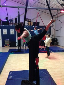 TW Editor, Alexa, practicing a Rebecca split in a beginner aerial silks class