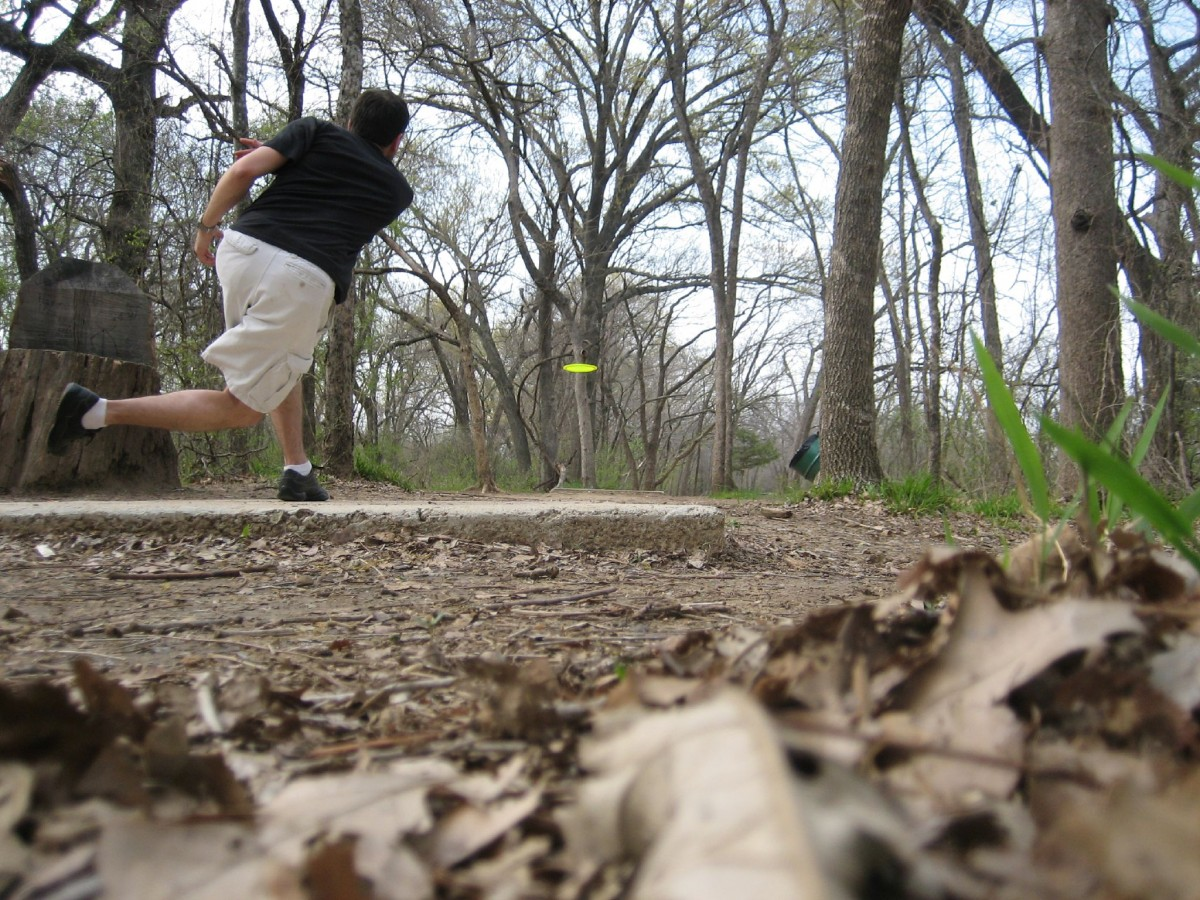 disc golf player throwing a drive